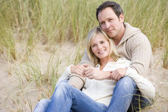 Couple sitting on beach smiling Royalty Free Stock Photos