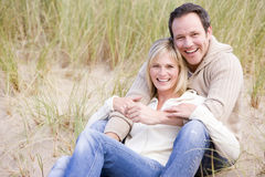 Couple sitting on beach smiling. At camera Stock Photos