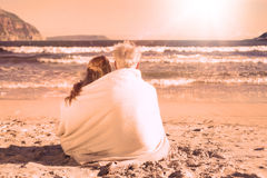 Couple sitting on the beach under blanket looking out to sea Stock Photography