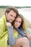 Couple sitting on the beach under blanket, relaxing and enjoying themselves Stock Photo