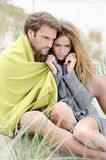 Couple sitting on the beach under blanket, relaxing and enjoying themselves Royalty Free Stock Images