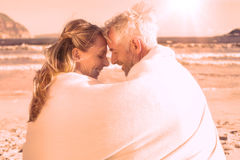 Couple sitting on the beach under blanket smiling at each other Royalty Free Stock Images