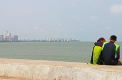 Couple sitting on beach wall mumbai india Stock Images