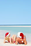 Couple Sitting On Beach Wearing Santa Hats Royalty Free Stock Images