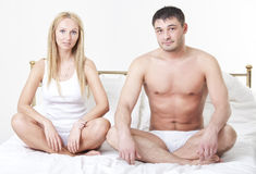 Couple sitting on bed Stock Images