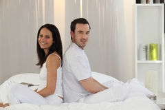 Couple sitting on a bed Stock Photos