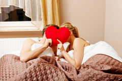 Couple sitting in bed and covering faces with heart pillow Stock Photo