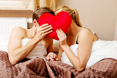 Couple sitting in bed and covering faces with heart pillow Stock Photography