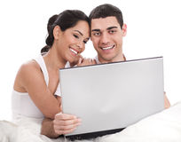 Couple sitting in bed with laptop Stock Images