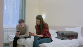 Couple sitting on the bed, not talking to each other after quarrel, typing on smartphones. Professional shot in 4K resolution. 068. You can use it e.g. in your stock footage
