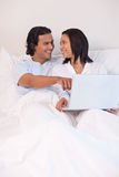 Couple sitting on the bed surfing the internet Stock Photo