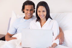 Couple sitting on the bed with their laptop Royalty Free Stock Image