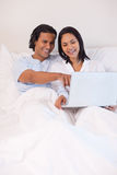 Couple sitting on the bed with their notebook Royalty Free Stock Photo