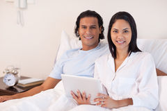 Couple sitting on the bed with their tablet pc Stock Photo
