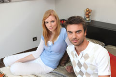 Couple sitting on a bed Royalty Free Stock Photos