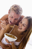 Couple sitting in bedroom eating cereal Royalty Free Stock Photos