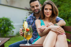 Couple sitting behind the table in garden and having colorful dr Royalty Free Stock Image