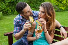 Couple sitting behind the table in garden and having colorful dr Stock Image