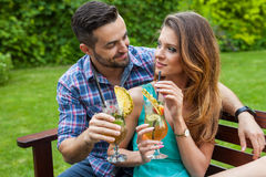 Couple sitting behind the table in garden and having colorful dr Royalty Free Stock Photo