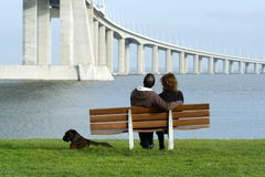 Couple sitting on a bench. Near the water Royalty Free Stock Image