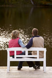 Couple sitting on a bench. At a lake in autumn royalty free stock images