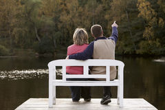 Couple sitting on a bench. At a lake in autumn stock image
