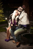 Couple sitting on bench in autumn park at night Royalty Free Stock Photo