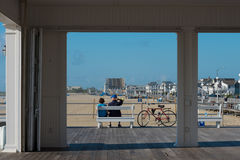 Couple  Sitting on a Bench on the Boardwalk. Avon-by-th-Sea, NJ USA -- Aug 4, 2016 Man and woman sit relaxing on a bench on the boardwalk. Editorial Use Only Royalty Free Stock Photos