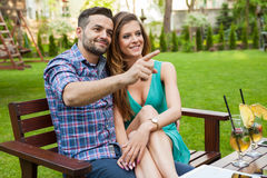 Couple sitting on the bench with drinks and spending great time. Stock Photos