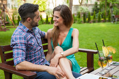 Couple sitting on the bench with drinks and spending great time. Stock Images