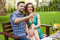 Couple sitting on the bench with drinks and spending great time. Royalty Free Stock Images