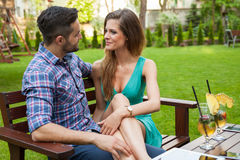 Couple sitting on the bench with drinks and spending great time. Royalty Free Stock Photo