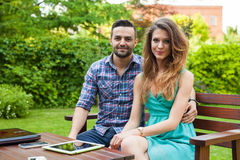 Couple sitting on the bench with drinks and spending great time. Stock Photography