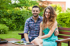 Couple sitting on the bench with drinks and spending great time. Stock Photo