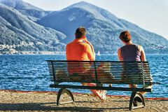 Couple sitting on bench in Ascona in Ticino canton Switzerland. Couple sitting on the bench at the embankment of the luxurious resort in Ascona on Lake Maggiore Royalty Free Stock Images