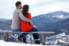Couple sitting on bench and enjoying mountain landscape, space for text. Winter vacation stock photo