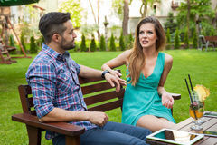 Couple sitting on the bench in the garden and arguing. Stock Photography