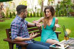 Couple sitting on the bench in the garden and arguing. Stock Photo