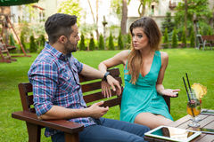 Couple sitting on the bench in the garden and arguing. Stock Image
