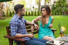 Couple sitting on the bench in the garden and arguing. Royalty Free Stock Image