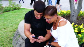 Couple sitting on the bench in the garden and using tablet and smartphone. They are looking into camera stock footage