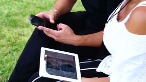 Couple sitting on the bench in the garden and using tablet and smartphone. They are looking into camera stock video