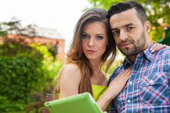 Couple sitting on the bench in the garden, using tablet and smil Royalty Free Stock Images