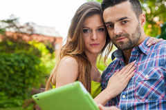 Couple sitting on the bench in the garden, using tablet and smil Stock Photography