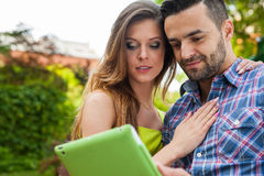 Couple sitting on the bench in the garden, using tablet and smil Royalty Free Stock Photography