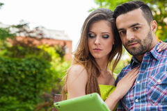 Couple sitting on the bench in the garden, using tablet and smil Stock Image
