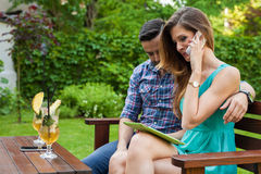 Couple sitting on the bench. Girl is talking by the phone and us Stock Images