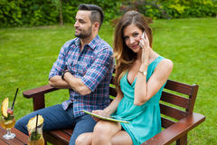 Couple sitting on the bench. Girl is talking by the phone and us Royalty Free Stock Image