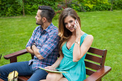 Couple sitting on the bench. Girl is talking by the phone and us Royalty Free Stock Photo