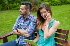 Couple sitting on the bench. Girl is talking by the phone and us Stock Photo